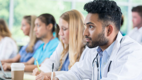 Male medical student attentively listens to professor during class. He is taking notes. His classmates are in the background.